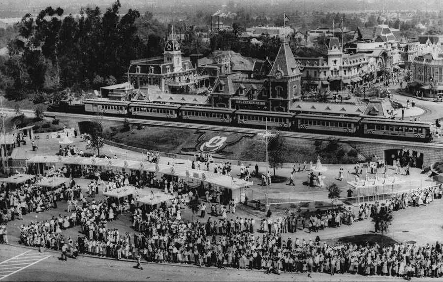 Hundreds of people wait in line for tickets to Walt Disney's 17-million dollar amusement park called Disneyland on July 18. 1955. The Disneyland and Sant Fe train which circles the park is stopped at the Disneyland entrance. The amusement park is near Anaheim, Ca.
