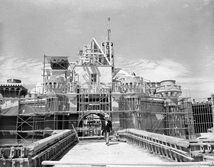 Walt Disney crosses the drawbridge that saves as the entrance to the castle in what will be the heart of Disneyland, in California on April 16, 1955. It's located at the end of Main Street and will house part of Fantasyland. This is the castle where you can see the dining hall awaiting the returning King Arthur's Knights, Sleeping Beauty slumbering, Peter Pan ride, Alice in Wonderland's story and many others.