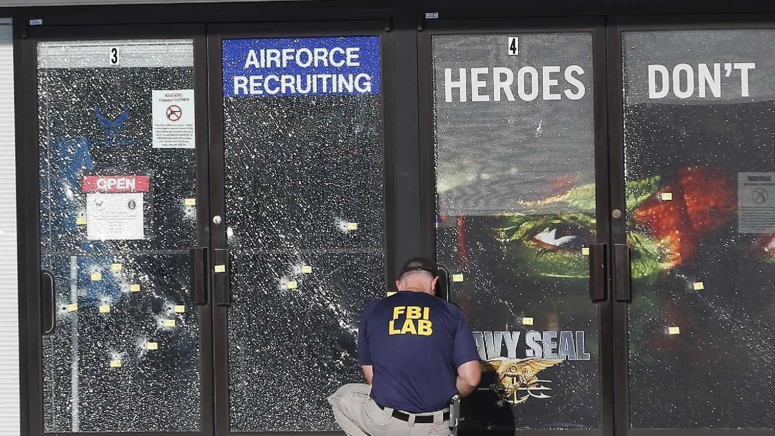An FBI investigator investigates the scene of a shooting outside a military recruiting center on Friday, July 17, 2015, in Chattanooga, Tenn. Muhammad Youssef Abdulazeez of Hixson, Tenn., attacked two military facilities on Thursday, in a shooting rampage that killed four Marines.