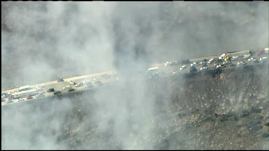 This photo from a TV helicopter shows the smoke and flames spreading to vehicles on Interstate 15 north of Los Angeles.