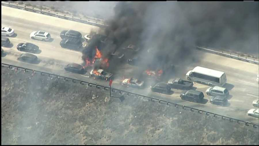 Several burnt-out cars sat on the highway as flames shot up from them.