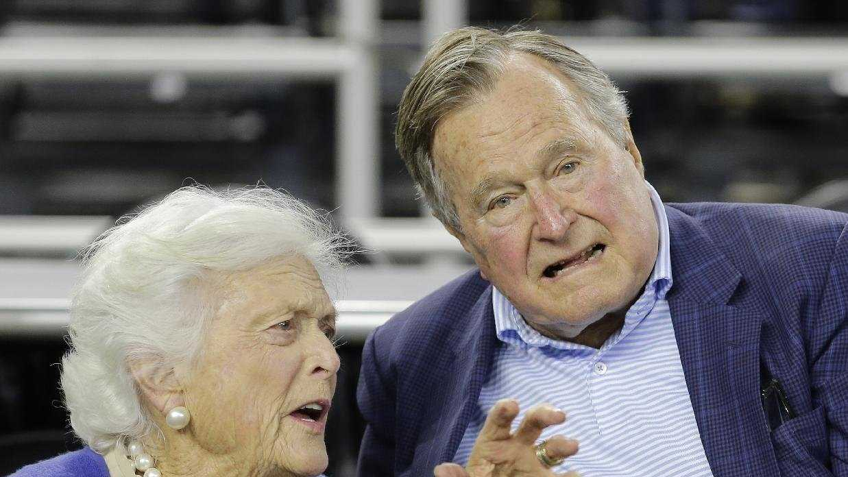In this March 29, 2015, file photo, former President George H.W. Bush and his wife Barbara Bush speak before the first half of an NCAAA college basketball game in Houston. A spokesman says doctors are pleased with the progress the former president is making since he fractured a bone in his neck during a fall. Jim McGrath said Sunday, July 19, 2015, that Bush is doing better and his spirits are good.