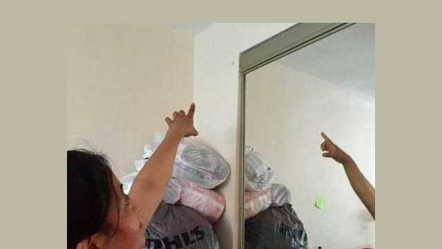Maria Bermejo points to a hole in the bedroom of her Castle Green apartment, where a stray bullet got lodged three feet above her infant son's crib early Sunday morning.