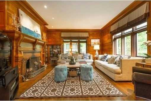 Awarm mellow wood paneled library w/beautifully hand-carved mantle.