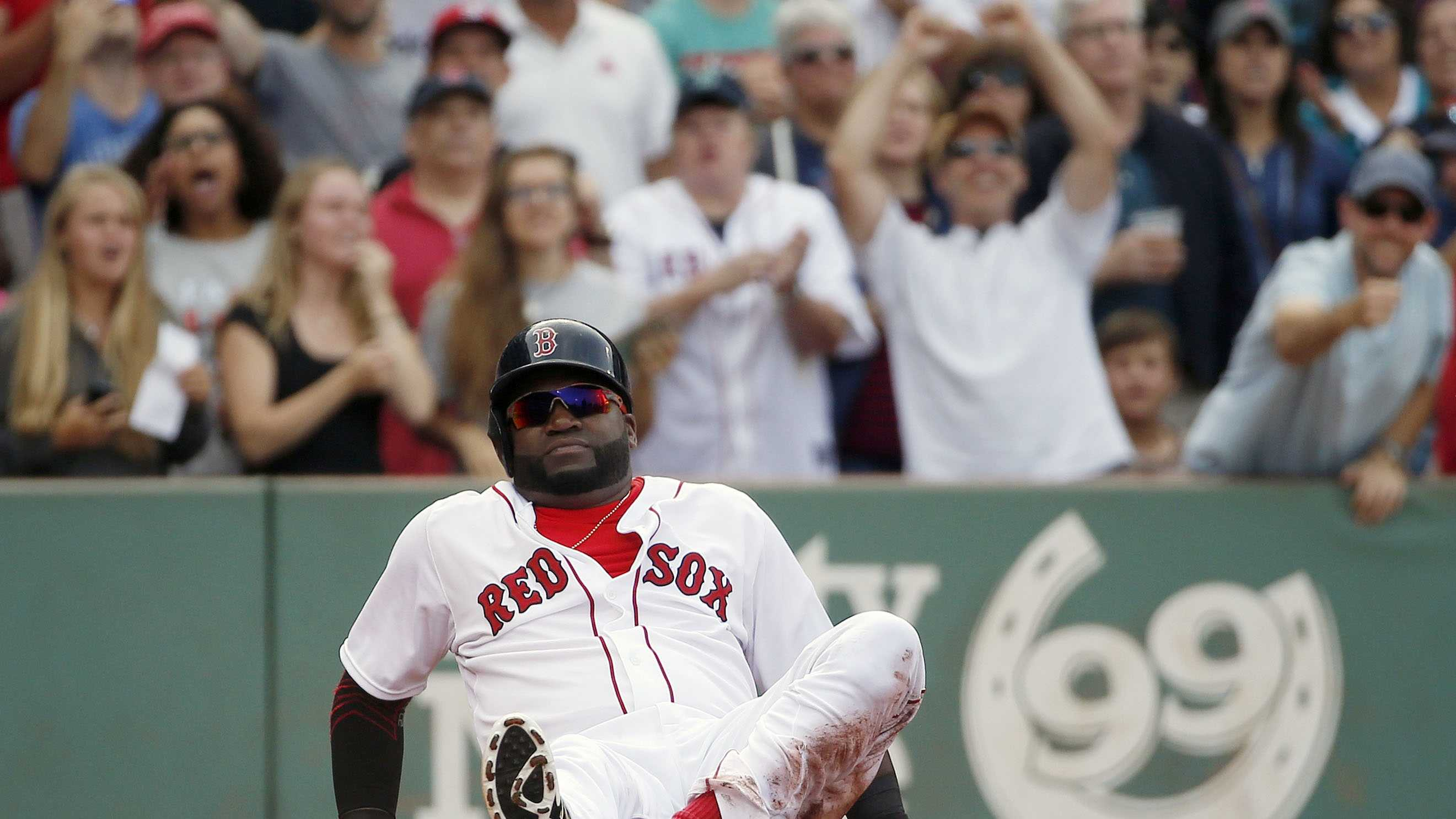 Boston Red Sox's David Ortiz sits on the ground after being tagged out at home plate trying to score on a single by Hanley Ramirez during the second inning of a baseball game against the Detroit Tigers in Boston, Saturday, July 25, 2015.