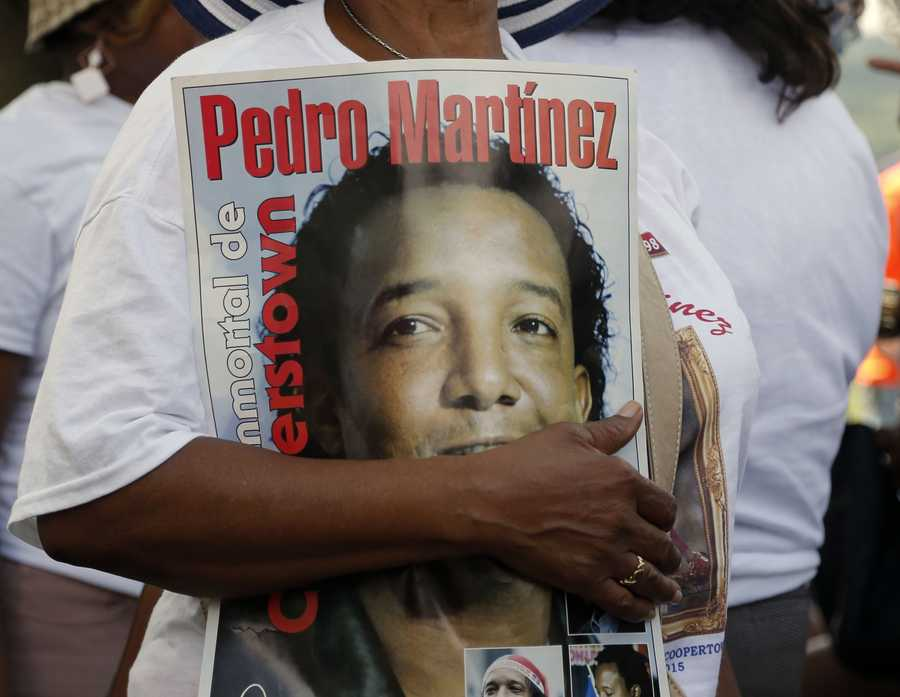 A Pedro Martinez fan carries a poster at the Clark Sports Center before the National Baseball Hall of Fame induction ceremony on Sunday, July 26, 2015, in Cooperstown, N.Y. Martinez will be inducted to the hall Sunday afternoon. (AP Photo/Mike Groll)