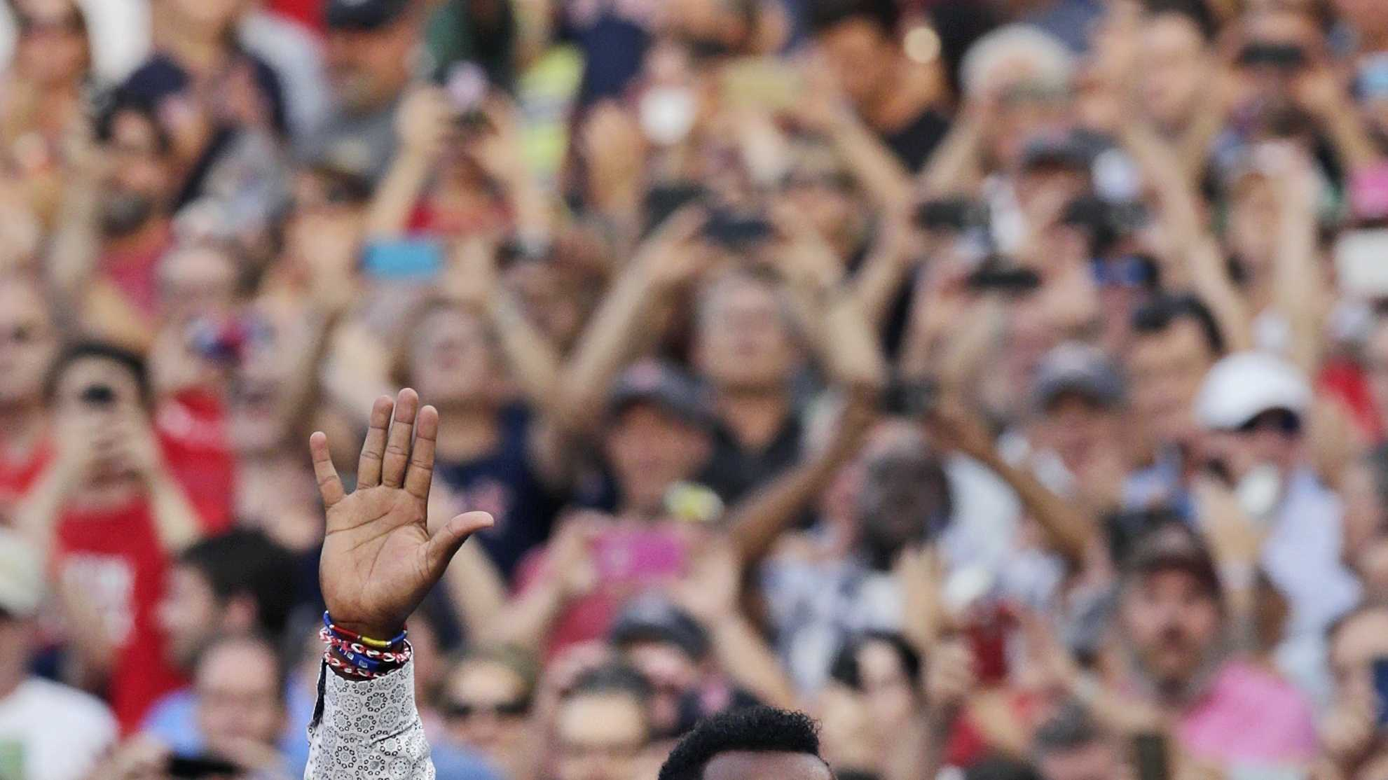 Baseball Hall of Fame member and former Boston Red Sox player Pedro Martinez acknowledges fans during a ceremony where his jersey was retired prior to a baseball game against the Chicago White Sox at Fenway Park in Boston, Tuesday, July 28, 2015. (AP Photo/Charles Krupa)