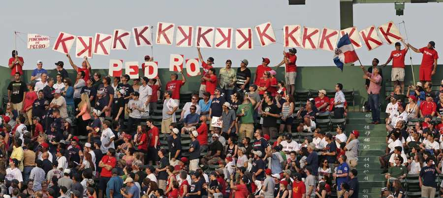 Red Sox fans honor Baseball Hall of Fame member and former Boston Red Sox player Pedro Martinez during a ceremony where his jersey was retired prior to a baseball game against the Chicago White Sox at Fenway Park in Boston, Tuesday, July 28, 2015. (AP Photo/Charles Krupa)