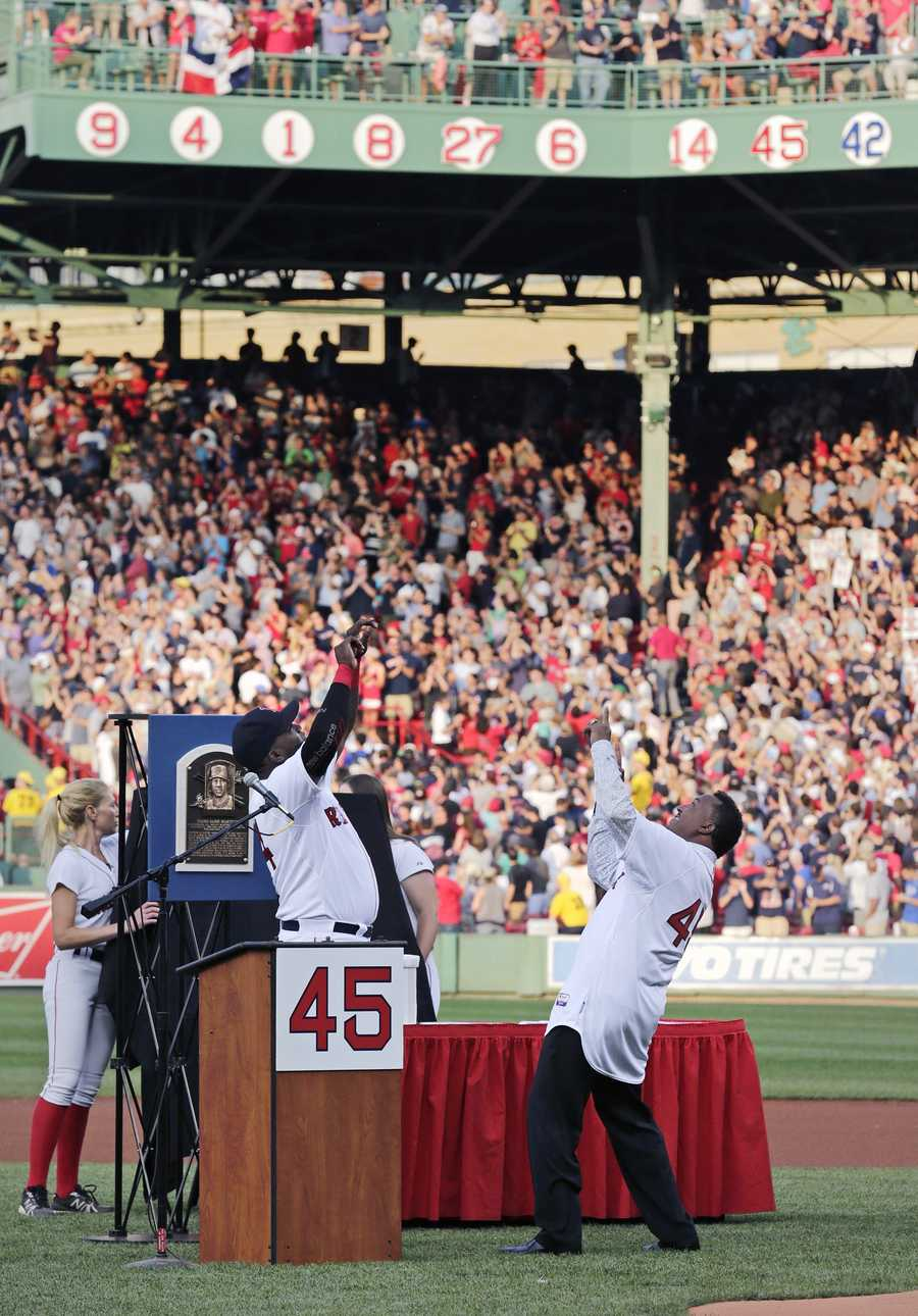 Baseball Hall of Fame member and former Boston Red Sox player Pedro Martinez, right, and former teammate David Ortiz celebrate after Martinez's No. 45 was unveiled on the facade of the right field grandstands during a ceremony prior to a baseball game against the Chicago White Sox at Fenway Park in Boston, Tuesday, July 28, 2015. (AP Photo/Charles Krupa)