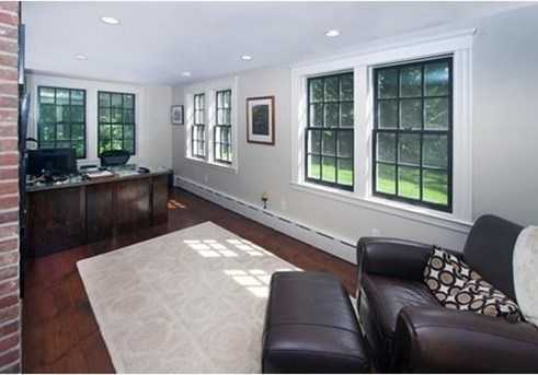 Private office and family room with fireplace overlooking mature landscaped backyard.