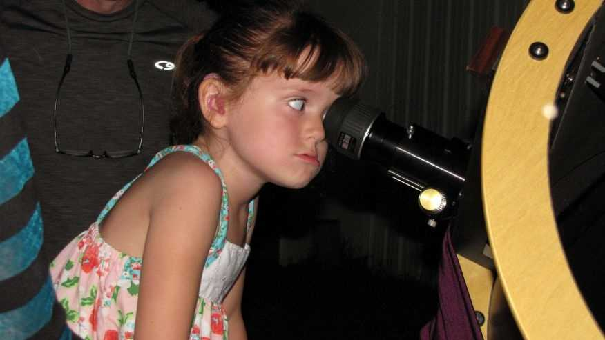 "In this July 28, 2015, photo, Elizabeth ""Lizzy"" Myers, 5, gazes through a telescope at the Warren Rupp Observatory in Bellville, Ohio. Myers' parents have come up with a ""bucket list"" of things they want her to see before a rare condition causes her to lose her sight."