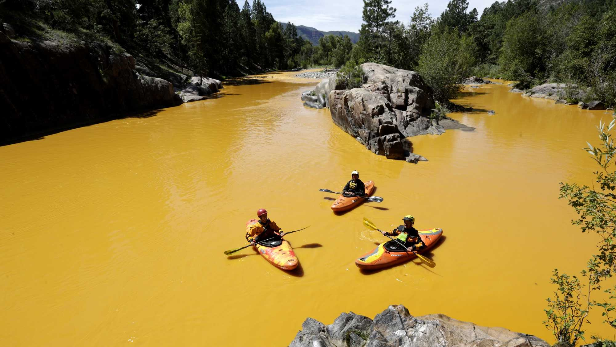 People kayak in the Animas River near Durango, Colo., Thursday, Aug. 6, 2015, in water colored from a mine waste spill. The U.S. Environmental Protection Agency said that a cleanup team was working with heavy equipment Wednesday to secure an entrance to the Gold King Mine. Workers instead released an estimated 1 million gallons of mine waste into Cement Creek, which flows into the Animas River.