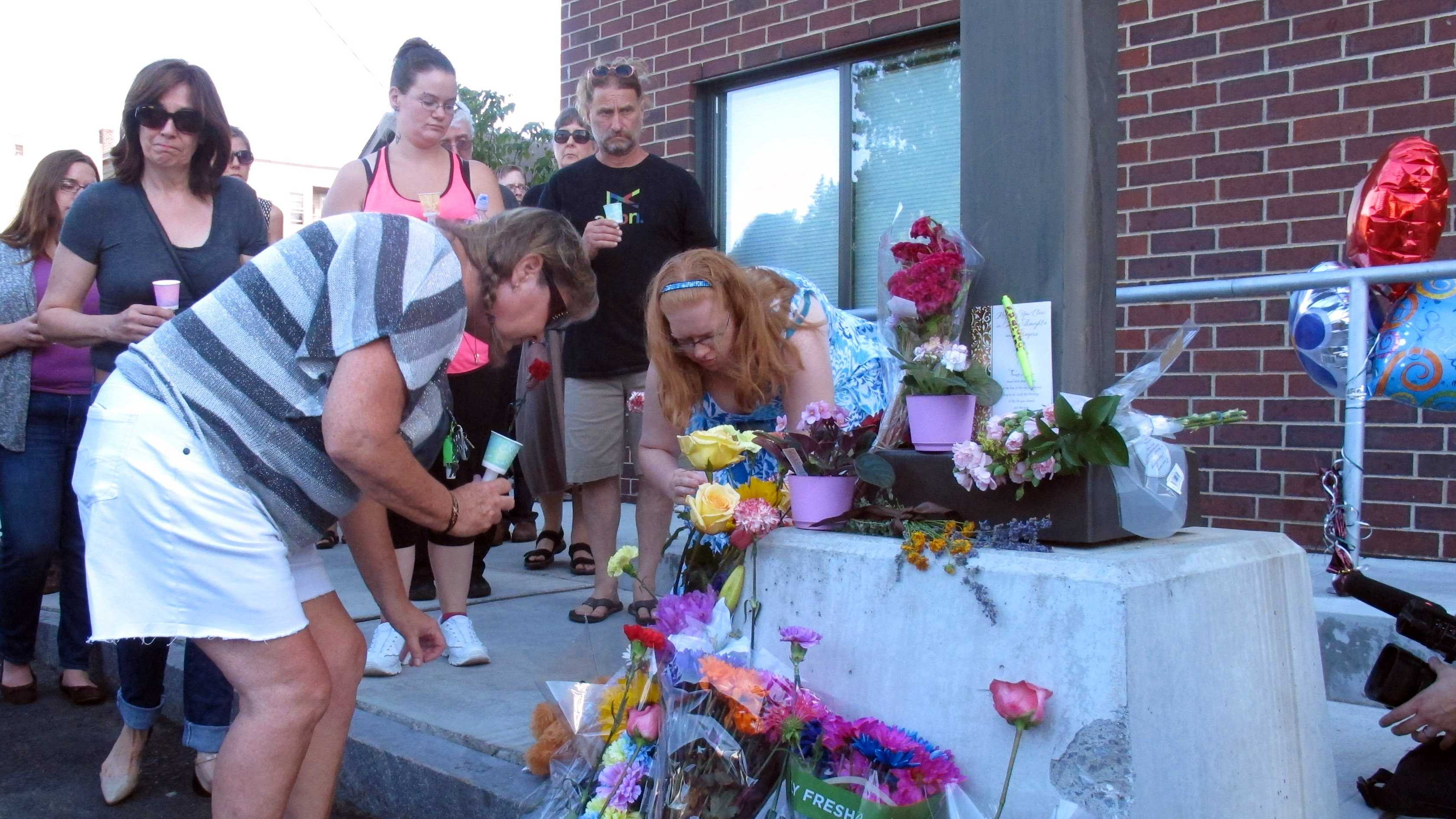 People place flowers, Sunday, Aug. 9, 2015, at the site where Vermont social worker Lara Sobel was killed on Friday in Barre, Vt. About 300 people attended a vigil that began at a labor hall and ended at the site where Sobel was shot Friday as she left work. Jody Herring, the woman charged with Sobel's death, is due in court Monday.
