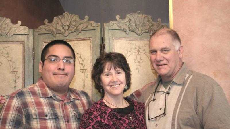Tomas Clark, at left, poses for a photo with his parents, Jeannine and Thomas Clark, at a family party.