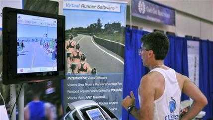 Joe Ciavattone, an employee of Outside Interactive, demonstrates the company's virtual race technology at the New Balance Falmouth Road Race expo in Falmouth, Mass. The company is partnering with the race to let runners compete on a treadmill virtually from anywhere while watching video footage of the actual 7-mile course.