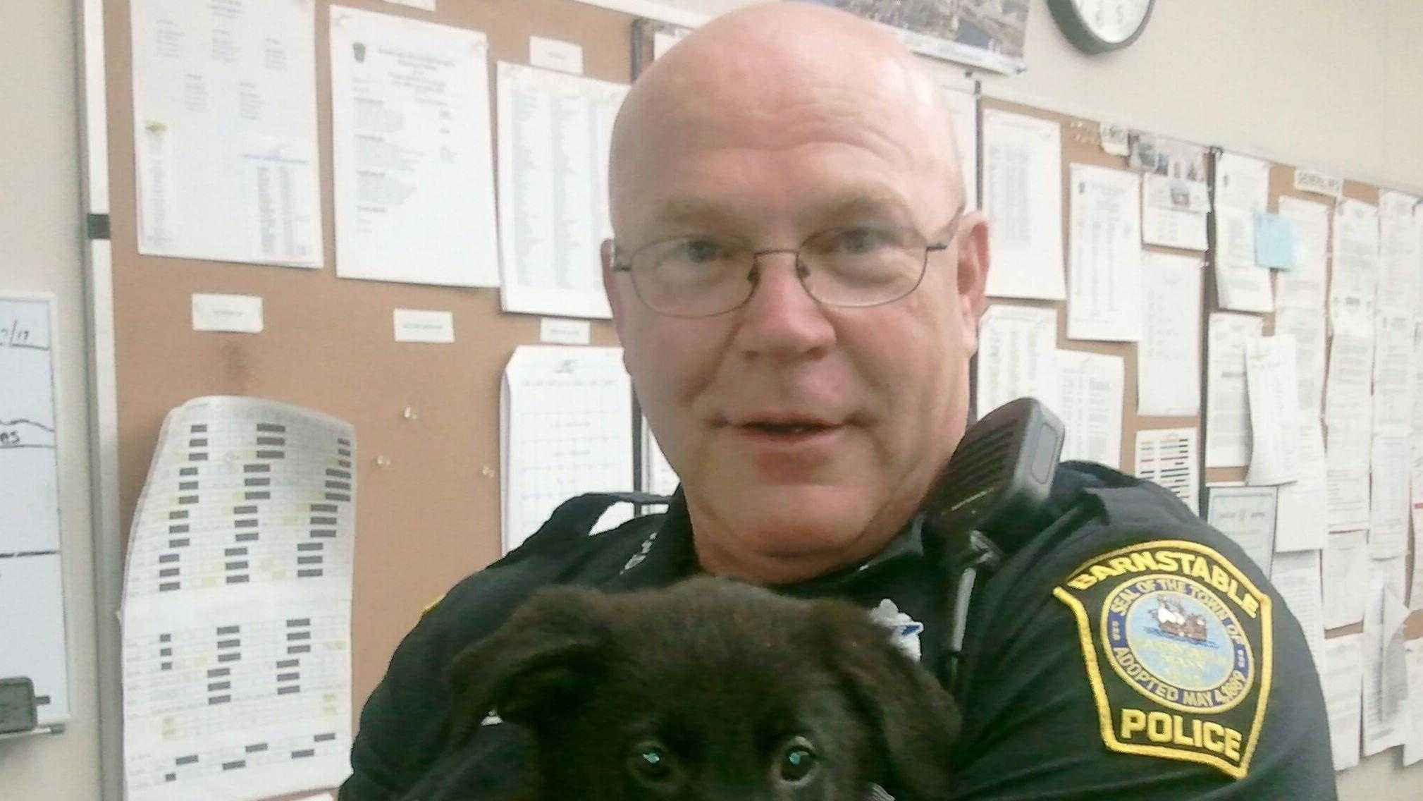 "Barnstable police officer James Melia with ""Midnight."""
