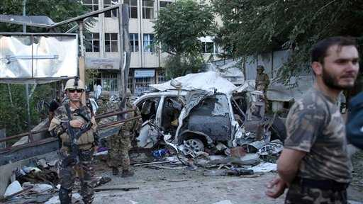 Afghan security forces and British soldiers inspect the site of a suicide attack in the heart of Kabul, Afghanistan, Saturday, Aug. 22, 2015. The suicide car bomber attacked a NATO convoy traveling through a crowded neighborhood in Afghanistan's capital Saturday, killing at least 10 people, including three NATO contractors, authorities said.