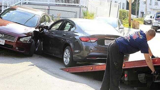 A tow driver from Lynch's Towing tows a rental car, a Chrysler 200, that hit a parked car on River Street and that was involved in a shooting on Menlo Street in Brockton on Sunday, Aug. 30,2015.