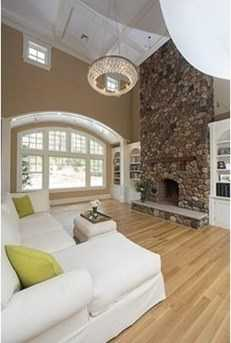 Grand foyer with custom moldings, and dramatic 2-story family room with floor to ceiling river stone fireplace.