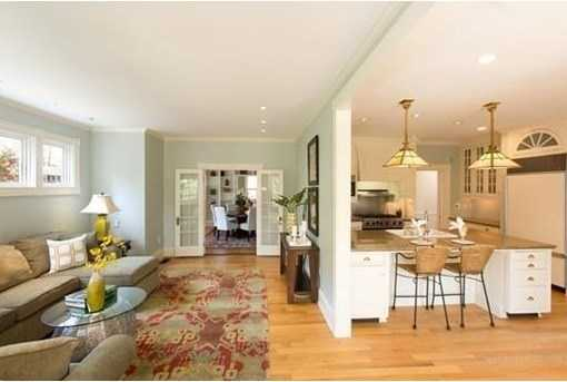 Inviting family room off the kitchen opens to a fireplaced dining room and living room with charming built-ins and tall windows flooded with sunshine.