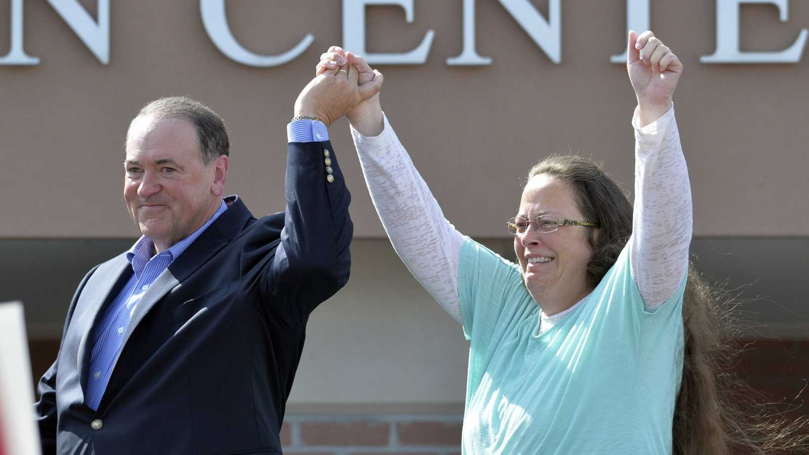 Rowan County Clerk Kim Davis, with Republican presidential candidate Mike Huckabee, left, at her side, greets the crowd after being released from the Carter County Detention Center, Tuesday, Sept. 8, 2015, in Grayson, Ky. Davis, the Kentucky county clerk who was jailed for refusing to issue marriage licenses to gay couples, was released Tuesday after five days behind bars.