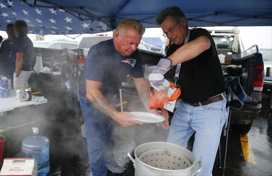 Lenny MacLeod, right, serves a lobster to Billy Burrows as they spend time tailgating in the parking lot before an NFL football game between the New England Patriots and the Pittsburgh Steelers Thursday, Sept. 10, 2015, in Foxborough, Mass. (AP Photo/Winslow Townson)