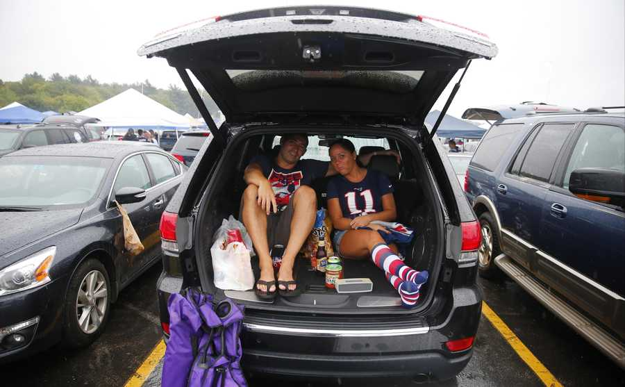 New England Patriots fans Aaron and Jillian Canales spend time tailgating in the parking lot before an NFL football game against the Pittsburgh Steelers Thursday, Sept. 10, 2015, in Foxborough, Mass. (AP Photo/Winslow Townson)