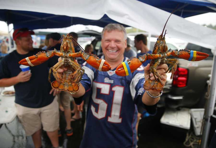 New England Patriots fan Clayton Witham from Maine brought lobsters as he spends time tailgating with friend in the parking lot before an NFL football game against the Pittsburgh Steelers Thursday, Sept. 10, 2015, in Foxborough, Mass. (AP Photo/Winslow Townson)
