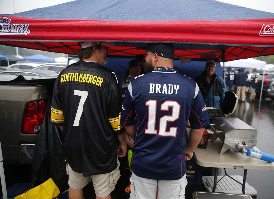 Pittsburgh Steelers fan Andy Chancey, left, and New England Patriots fan Chad Marchand spend time tailgating in the parking lot before an NFL football game between the New England Patriots and the Pittsburgh Steelers Thursday, Sept. 10, 2015, in Foxborough, Mass. (AP Photo/Winslow Townson)