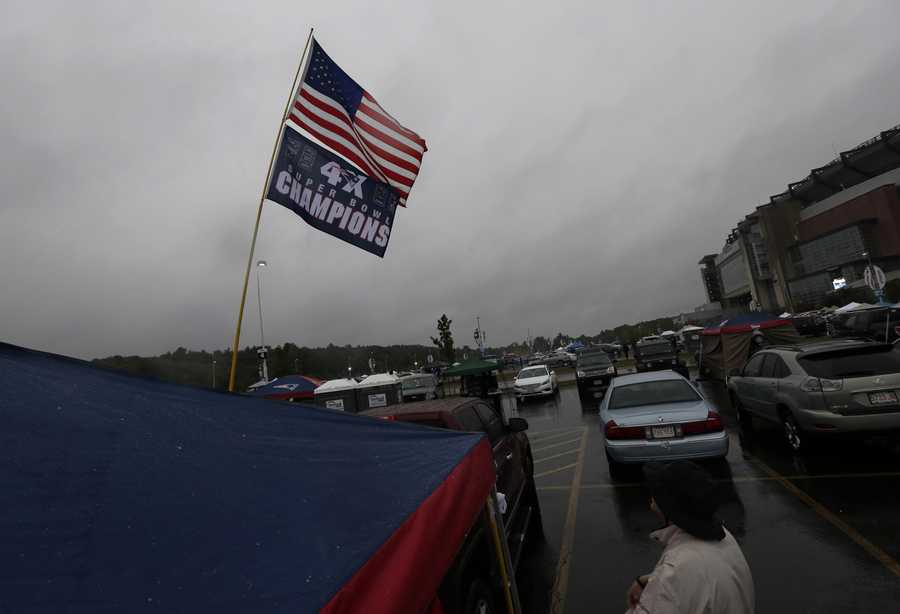 A banner proclaims the New England Patriots four-time Super Bowl champions as fans spend time tailgating in the parking lot before an NFL football game between the Patriots and the Pittsburgh Steelers Thursday, Sept. 10, 2015, in Foxborough, Mass. (AP Photo/Charles Krupa)