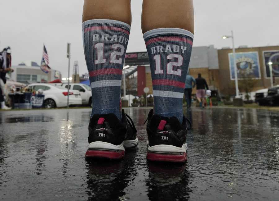 A New England Patriots fan wears socks supporting New England Patriots quarterback Tom Brady as she arrives for an NFL football game between the Patriots and the Pittsburgh Steelers Thursday, Sept. 10, 2015, in Foxborough, Mass. (AP Photo/Charles Krupa)