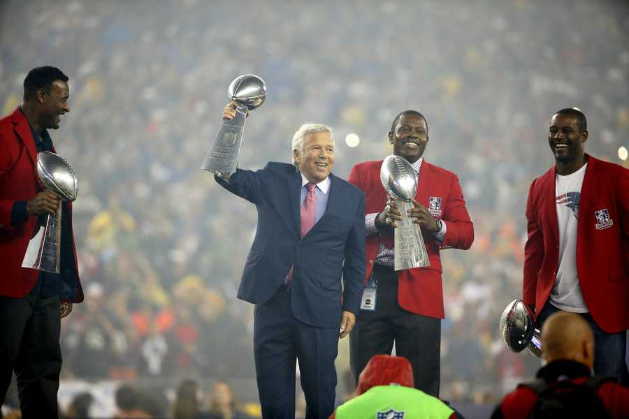 New England Patriots owner Robert Kraft, center, hoists the Lombardi Trophy for his team's win of Super Bowl XLIX as Patriots veterans hold the team's other three Lombardi trophies before an NFL football game against the Pittsburgh Steelers, Thursday, Sept. 10, 2015, in Foxborough, Mass. (AP Photo/Winslow Townson)
