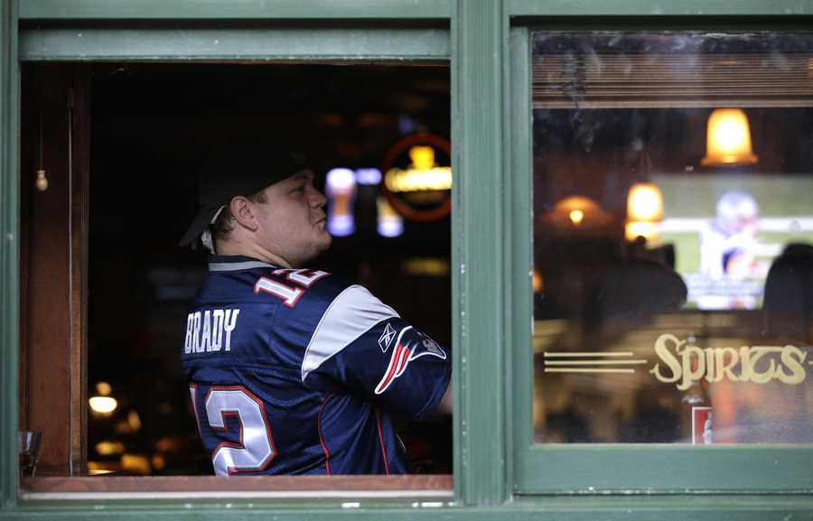 Jesse Hibbs, of Chicago, watches a big screen television at Brendan's Pub before an NFL football game against the Pittsburgh Steelers and the New England Patriots, Thursday, Sept. 10, 2015, in Chicago. Friends who are Patriots fans are coming to town, and you need to find a sports bar where they won't get booed out of the joint when glamour-boy quarterback Tom Brady gets rolling. (AP Photo/Nam Y. Huh)