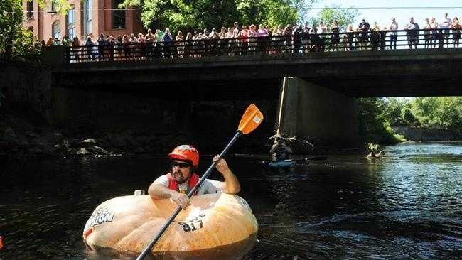 Todd Sandstrum of Easton takes a pumpkin on a 7-mile world record ride down the Taunton River on Saturday, Sept. 5, 2015.