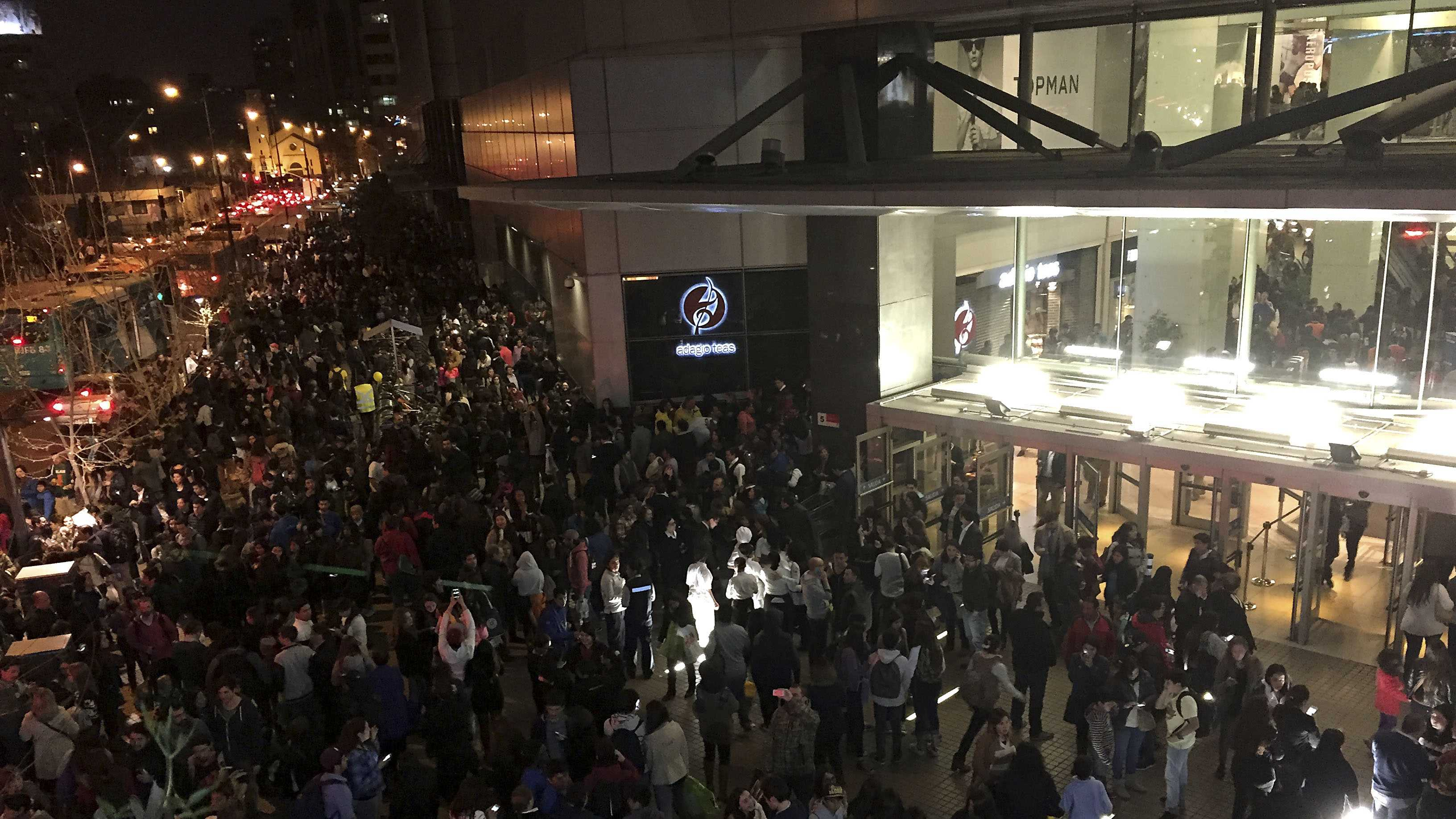 People evacuate a mall in Santiago after a powerful earthquake, in Santiago, Chile, Wednesday, Sept. 16, 2015. The magnitude-8.3 earthquake hit off Chile's northern coast causing buildings to sway in Santiago and other cities and sending people running into the streets. Authorities reported one death in a town north of the capital.(Nadia Perez/AGENCIA UNO via AP)