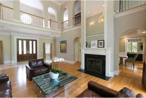 The dramatic, custom-designed interior features tall ceilings, arched entryways, gleaming hardwood and multiple two-sided fireplaces.