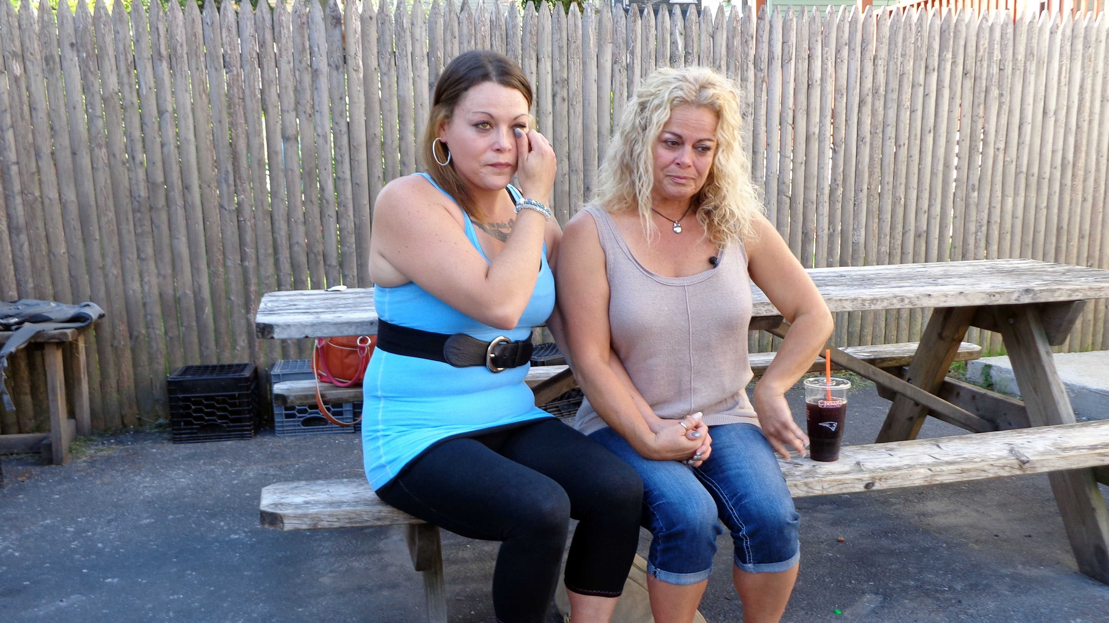 In this Sept. 18, 2015, photo, Kylee Moriarty, left, and her mother, Jackie Law, sit together outside the halfway house in Boston where Moriarty resided. This was their first meeting in person in more than a year. Moriarty is among more than 200 addicts taking advantage of a unique program offered by police in Gloucester, in which heroin addicts are fast-tracked into treatment rather than arrested.