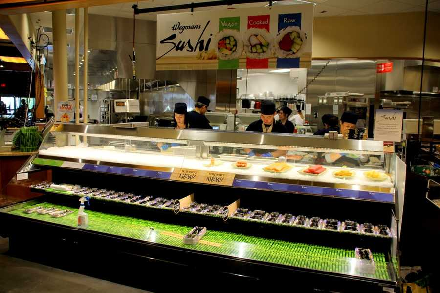 Workers at the Sushi bar are working on the display. Sushi is available in different varieties to customers.
