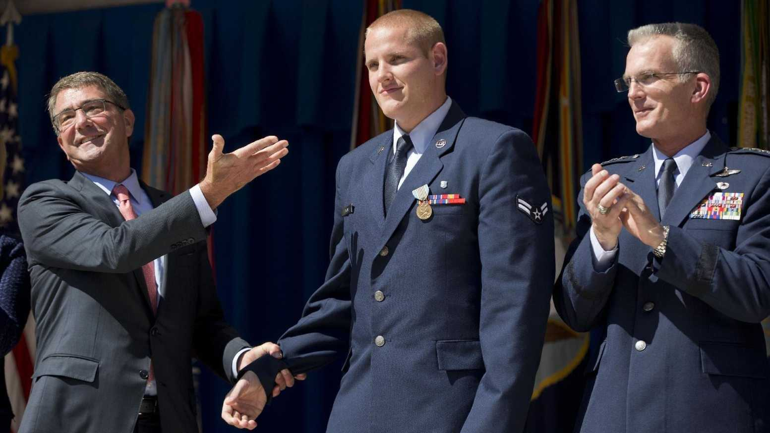 Defense Secretary Ash Carter, left, gestures towards Airman 1st Class Spencer Stone, center, before awarding Stone with the Airman's Medal and Purple Heart medal, during a ceremony with Joint Chiefs Vice Chairman Gen. Paul Selva, right, at the Pentagon, Thursday, Sept. 17, 2015. Stone along with Oregon National Guardsman Alek Skarlatos and Anthony Sadler where honored for heroically subduing a gunman on a Paris-bound passenger train last month.