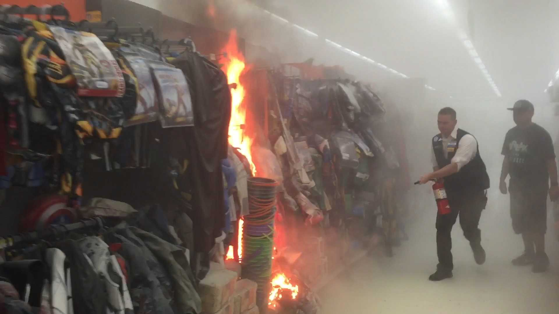 A Walmart employee uses a fire extinguisher to help contain a blaze set in the costume aisle of the store on Tuesday, Oct. 13, 2015.