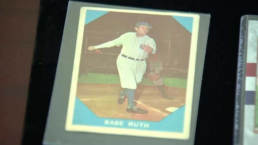 Among the items on display are a 1949 Red Sox banner and a Babe Ruth baseball card.