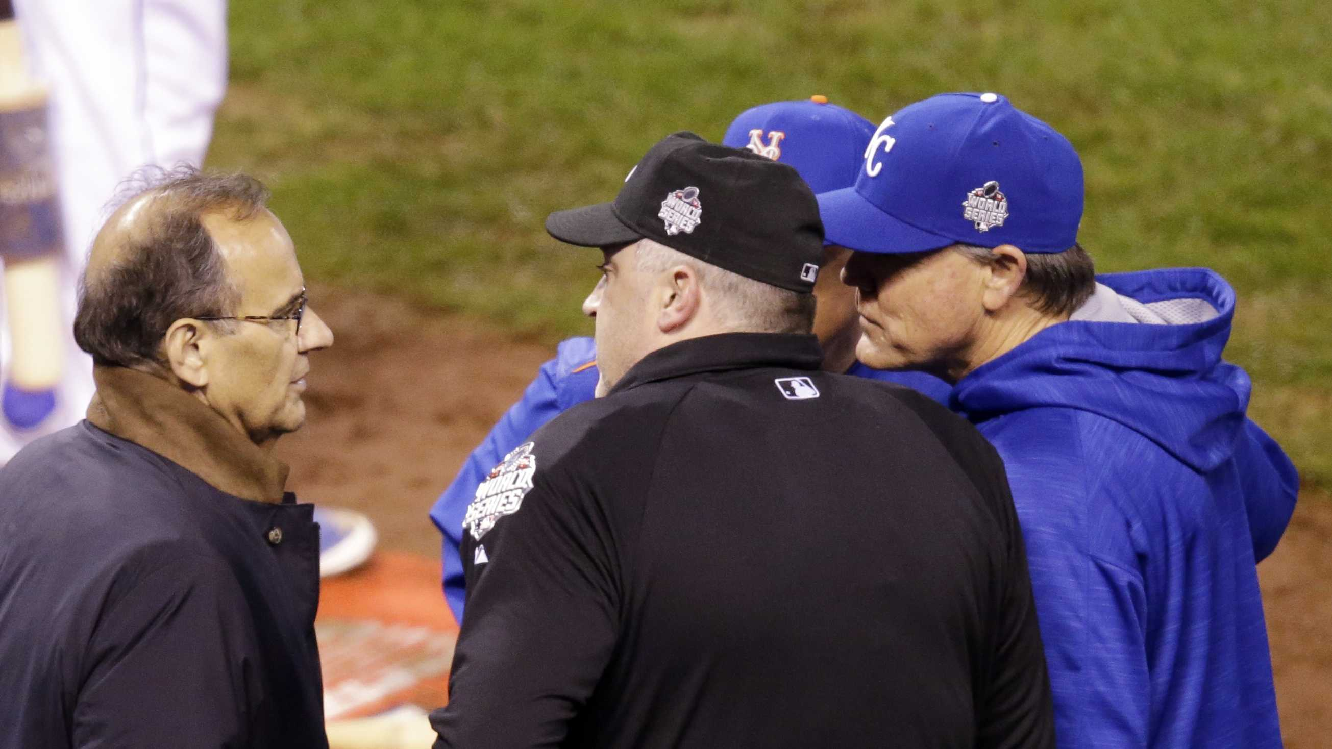 Executive Vice President for Baseball Operations Joe Torre talks to New York Mets manager Terry Collins and Kansas City Royals manager Ned Yost during a television technical interruption during the fourth inning of Game 1 of the Major League Baseball World Series Tuesday, Oct. 27, 2015, in Kansas City, Mo. (AP Photo/David Goldman)