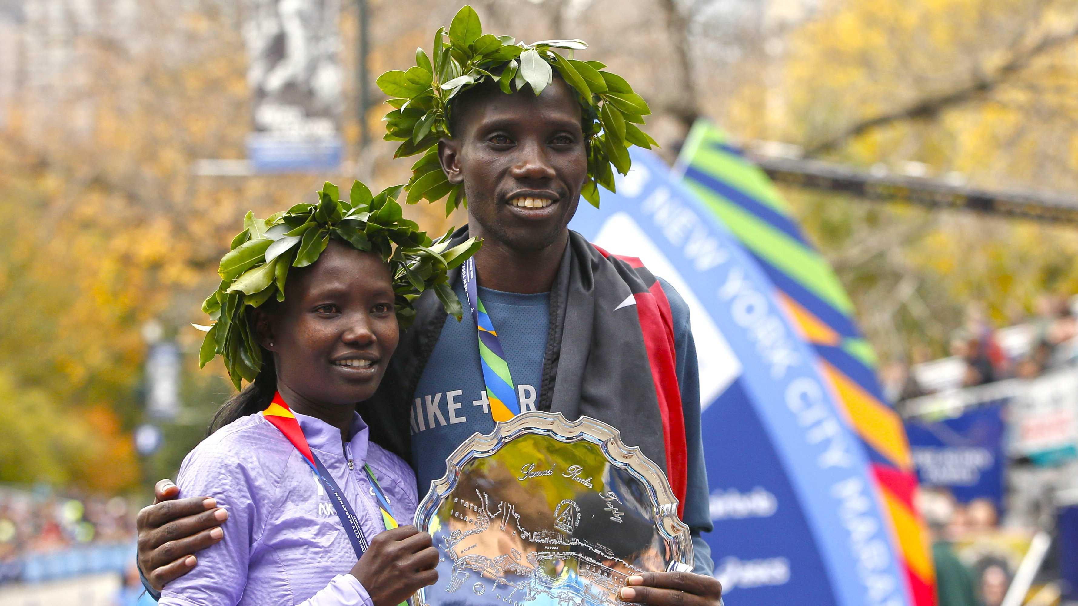 New York City marathon winners Mary Keitany and Stanley Biwott, both of Kenya, pose for photographers on the finish line of the the New York City marathon, Sunday, Nov. 1, 2015 in New York.