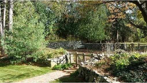 Lush private landscape with patio and stone-walled garden created from the foundation of antique barn.