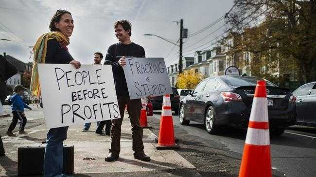 Jenn Vanola of Hyde Park and Justin Cifello of Buzzard's Bay hold signs during a rally and protest at Spectra's West Roxbury Lateral gas pipeline construction site in West Roxbury, Nov. 7, 2015.