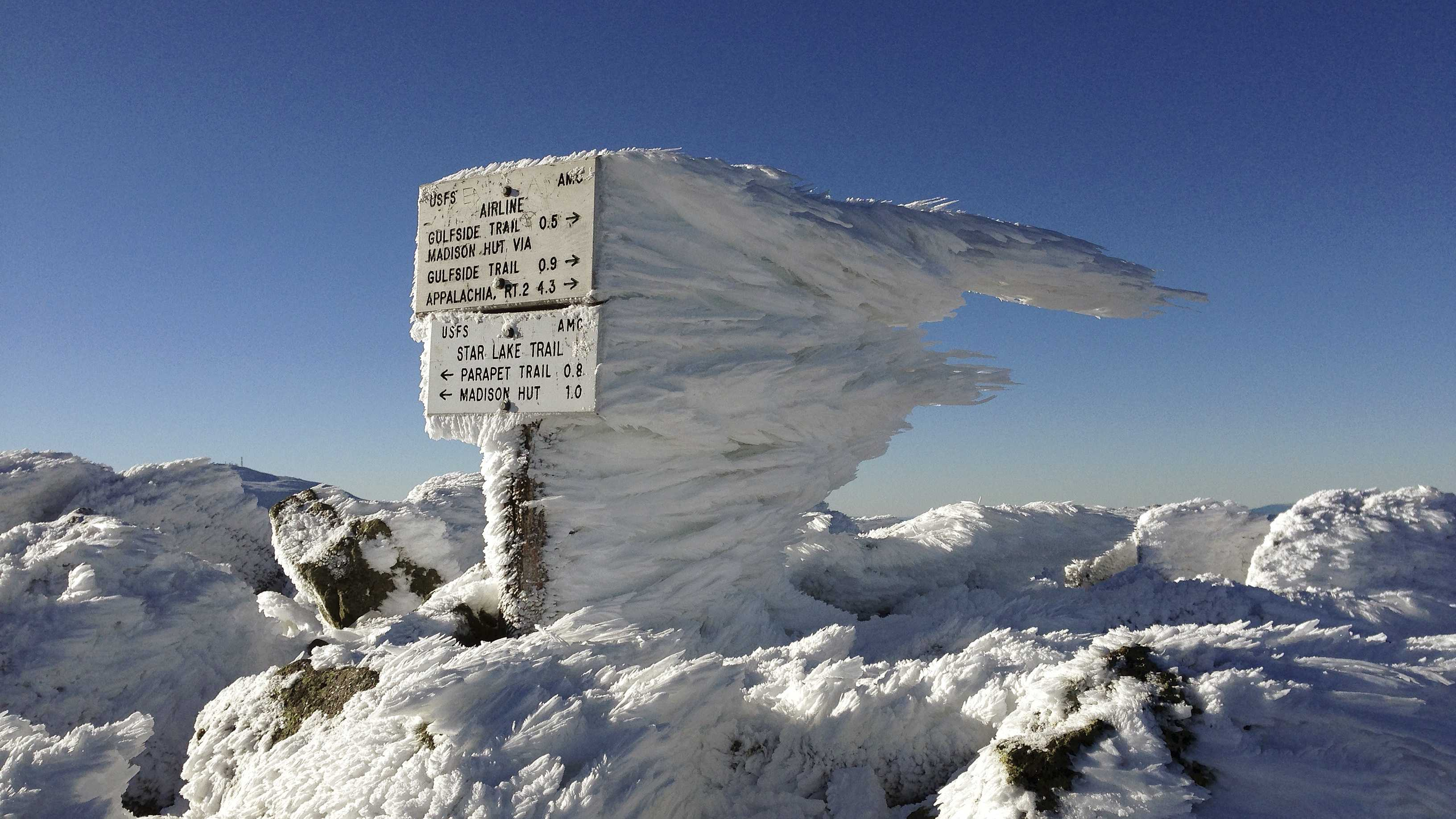 Rime ice extends several feet horizontally from a sign marking the summit of 5,774-foot Mount Adams, the second highest mountain in New England, on Tuesday, Nov. 17, 2015, in northern New Hampshire. Monday's freezing fog and strong winds formed the rime ice, creating a winter wonderland above treeline in New Hampshire's aptly named White Mountains.