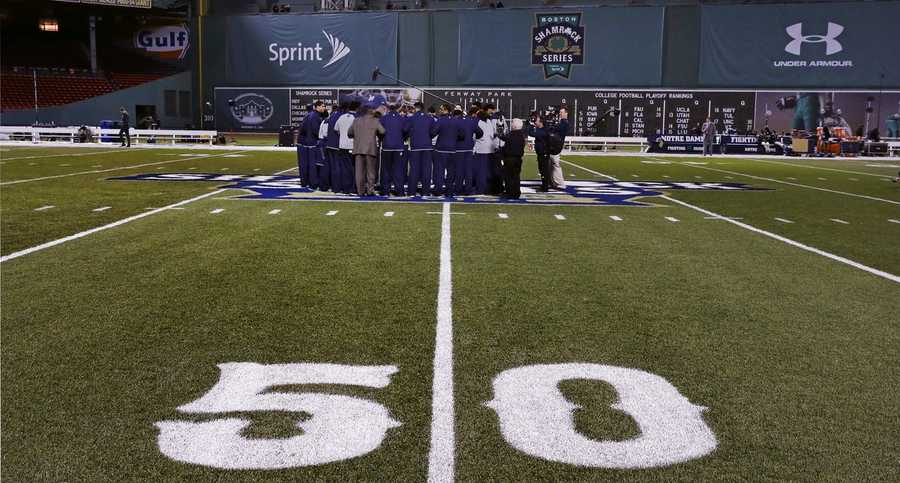 The Notre Dame football team huddles at the 50-yard line, near the foot of the Green Monster scoreboard, shortly after arriving at Fenway Park, home of the Boston Red Sox, prior to the Shamrock Series NCAA college football game against Boston College in Boston, Saturday, Nov. 21, 2015.