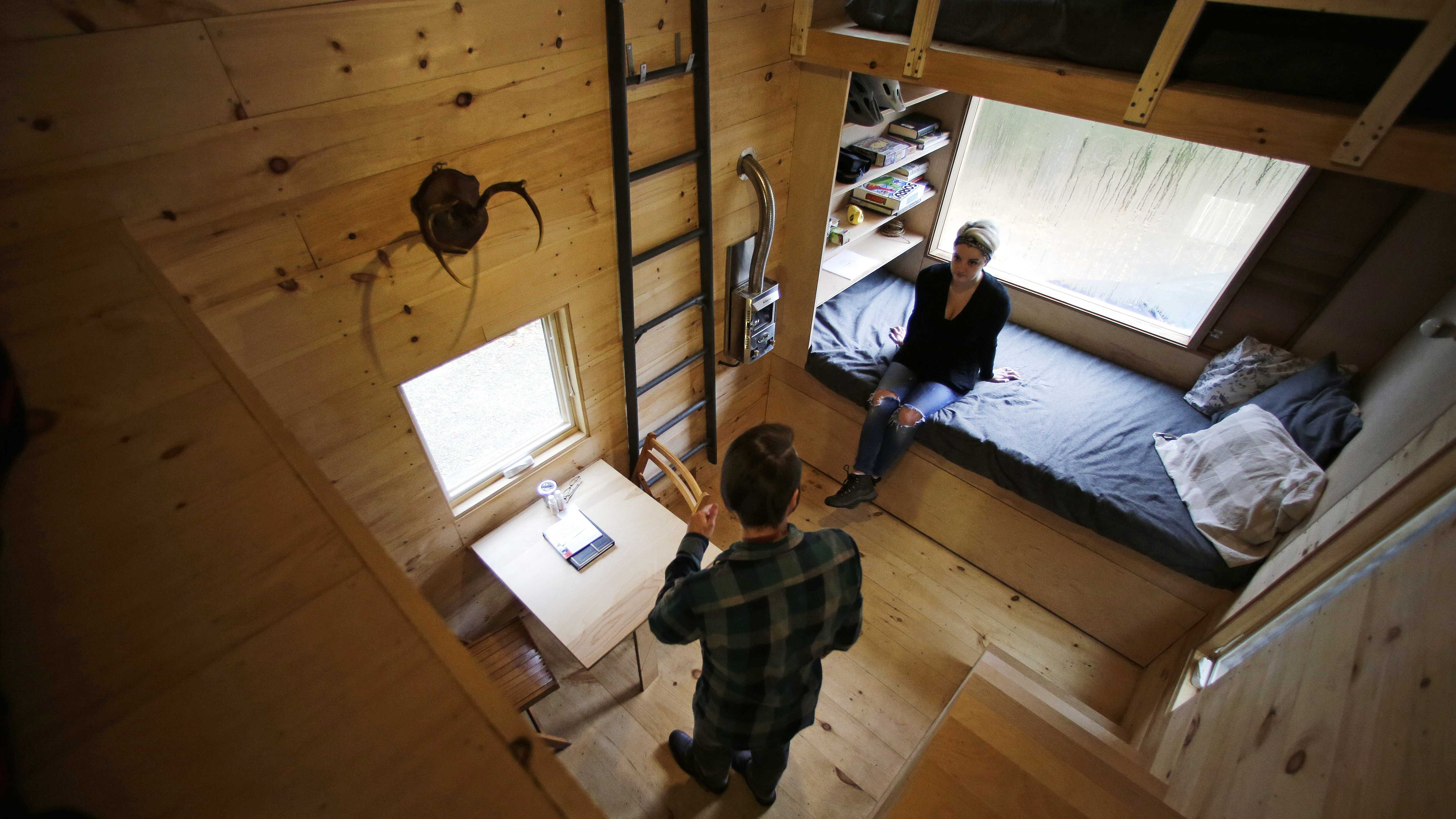 "In this Tuesday, Oct. 20, 2015 photo, Shane Lentz, of Pittsburgh, Pa., and his wife Hilary, talk before leaving a tiny house, which they rented for a weekend, in Croydon, N.H. As the tiny house phenomenon sweeps the nation, Harvard's Millennial Housing Lab thinks a tryout is in order for people toying with radically downsizing their lives. Its new ""Getaway"" project gives the curious an opportunity to spend a night or two in one of three tiny houses and get a real feel for the lifestyle before taking the plunge."