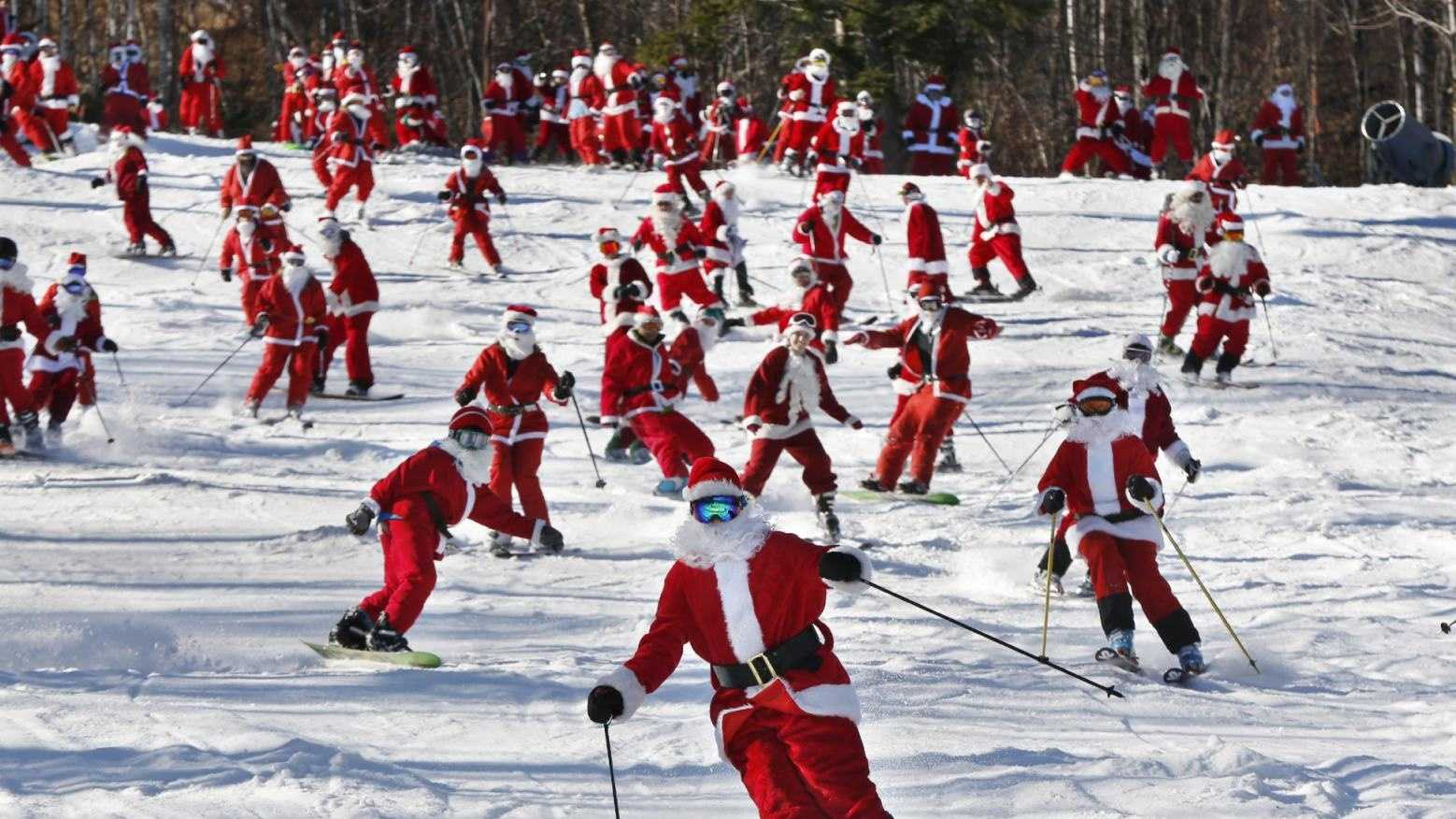 Skiers and snowboarders dressed as Santa take a run en masse at the Sunday River ski resort, Sunday, Dec. 6, 2015, in Newry, Maine. Skiers with full Santa outfits got free lift tickets for donating $15 to the Sunday River Community Fund.