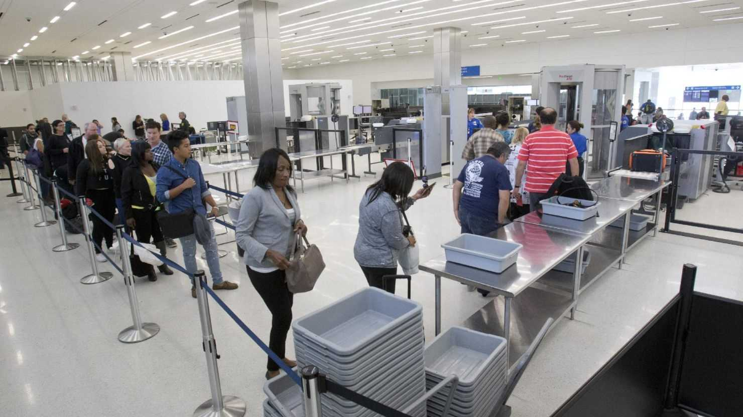 Passengers load their items into bins as they pass through security before flying out of the Fort Lauderdale-Hollywood International Airport, Friday, Dec. 18, 2015, in Fort Lauderdale, Fla. Transportation Security Administration spokesperson Sari Koshetz said that about 8,000 lbs. of prohibited items were confiscated this year by the TSA at the Fort Lauderdale airport.
